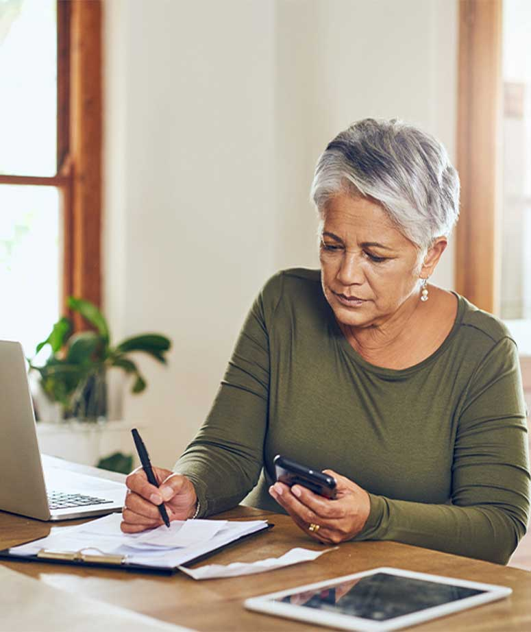 senior woman writes and looks at her phone