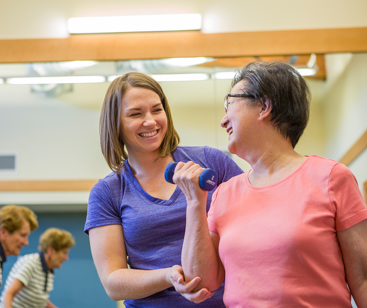 Senior woman doing exercises with a trainer
