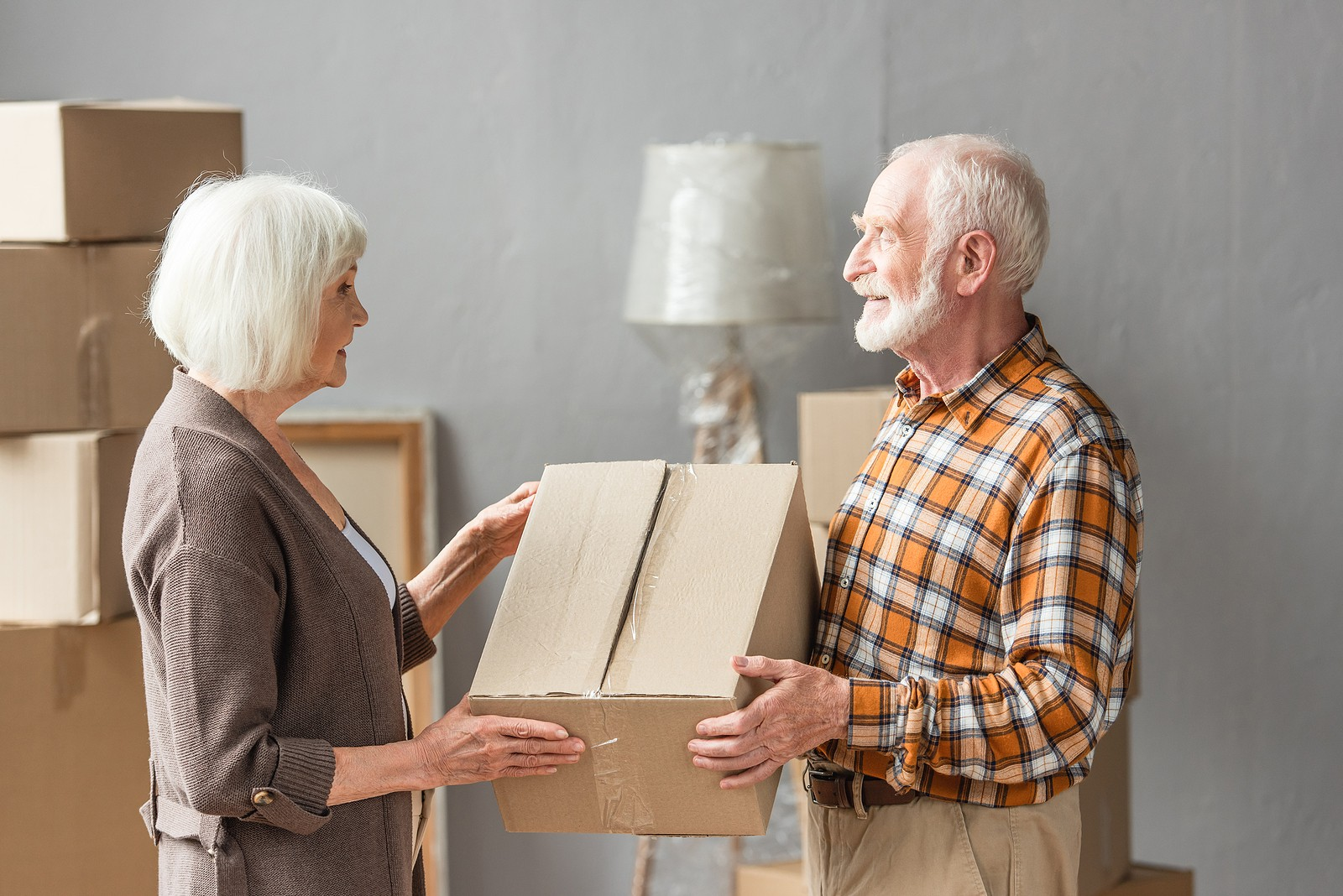Senior couple downsizing and packing up belongings together