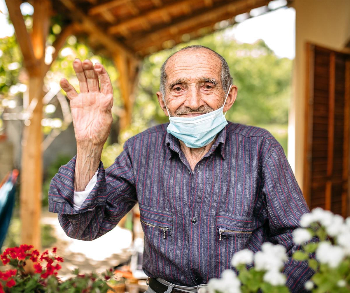 Older man wearing a mask waving