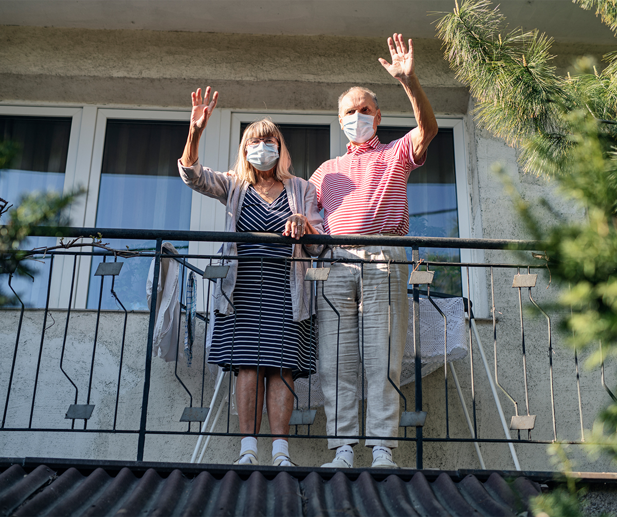 Older couple waving with masks