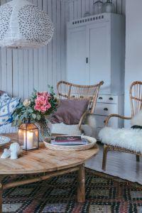 KUvassa olohuoneen kaksi tuolia, kukkia pöydällä ja lyhdyssä palaa kynttilä.