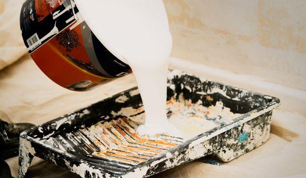 Kuvassa kaadetaan maalia maalipurkista alustalle.