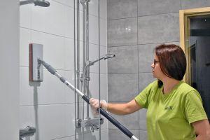 Kuvassa Miracle-palveluiden siivoojaa pesemässä kylpyhuoneen seiniä.
