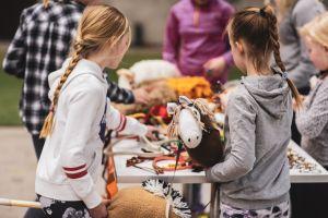 Keppihevosharrastajia tutkimassa myytäviä tuotteita Hevoset-messuilla