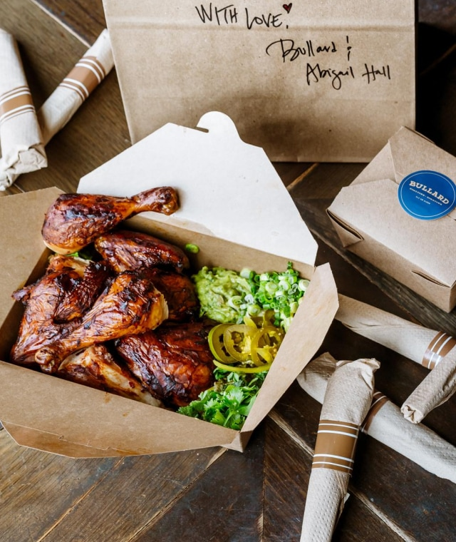 An open recycled waxed paper box with chicken wings, green onion, parsely, and pickled jalapeno. In the background is a paper bag with a handwritten message on it in marker.