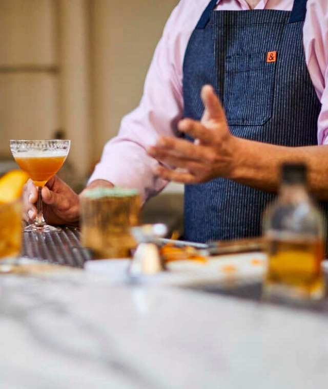 A closeup of a person wearing an apron talking about a cocktail in hand.