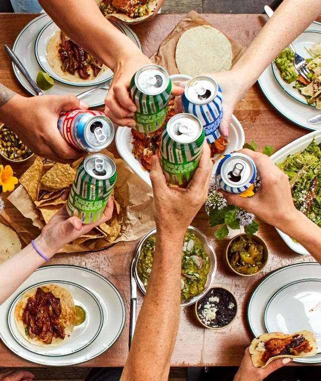 Overhead shot of six arms cheering canned drinks over a table covered with plates of tacos, chips, and toppings.