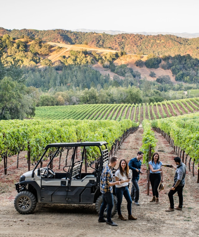 A group of people talking casually around a four wheel vehicle at a vineyard.