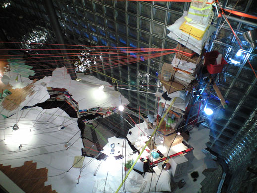 An 8m-high pile of various objects anchored to different beams and points in the space.