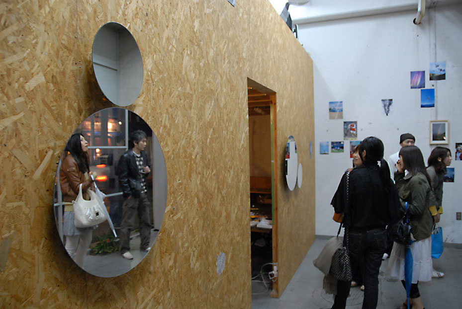 Morita's subtly rotating mirror works reflect the visitors at the opening.