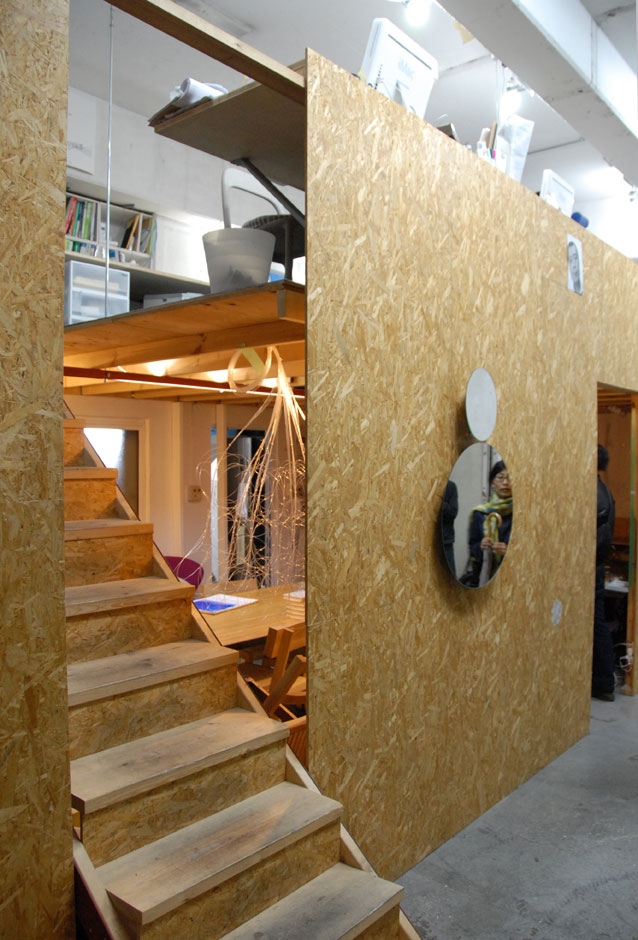 Director Hideaki Aoyama shares the space with architectural unit Schemata, which designed the wooden partitions which separate the exhibition space from the ground floor meeting area and the upstairs office space.