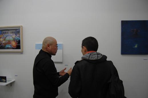 作品を前に編集者の小崎哲哉さんと話し込むディレクターの森裕一さん