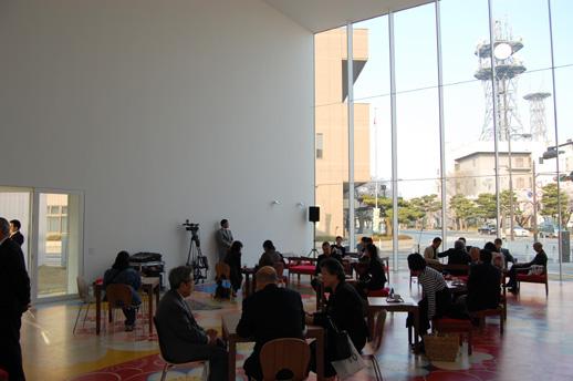 休憩スペースの内部。床には十和田市の伝統工芸である南部裂織をモチーフにしたマイケル・リンの作品。全体的に館内からは外部の都市空間を、外部の都市空間からは美術館の内部の様子を感じとることができる開放的なつくりが特徴。