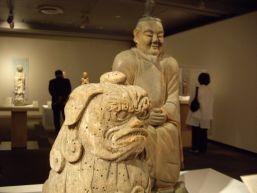 《狛犬吽形》滋賀県東近江市竹田神社蔵。《狛犬阿形》と対になっている。狛犬像は木喰の作品の中では非常に珍しい。後ろに写っているのは《神像》(香川県坂出市鴨神社蔵)。