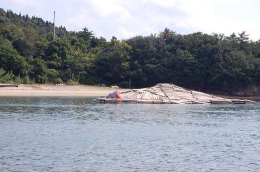 本村港の対岸にある島で漂流物を集め、大きな浮島を出現させています。オススメの鑑賞法は、家プロジェクト「護王神社」から本村港方面に峰を少し下ったところにある展望台から見下ろす方法。また本村港経由の高松〜豊島の航路が近くを通るほか、直島でレンタルバイクやクルージングサービスを提供しているT.V.C.SERVICEが見学ツアーを実施しています。