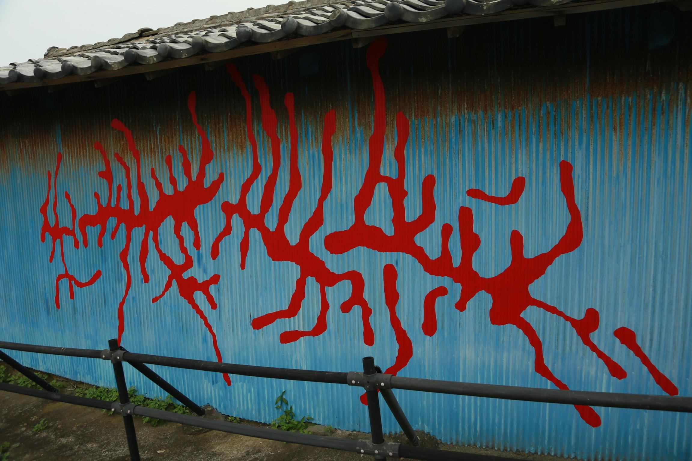 昆虫の這った跡を描いたペインティング。独特な赤色の絵の具を用いて製作されている