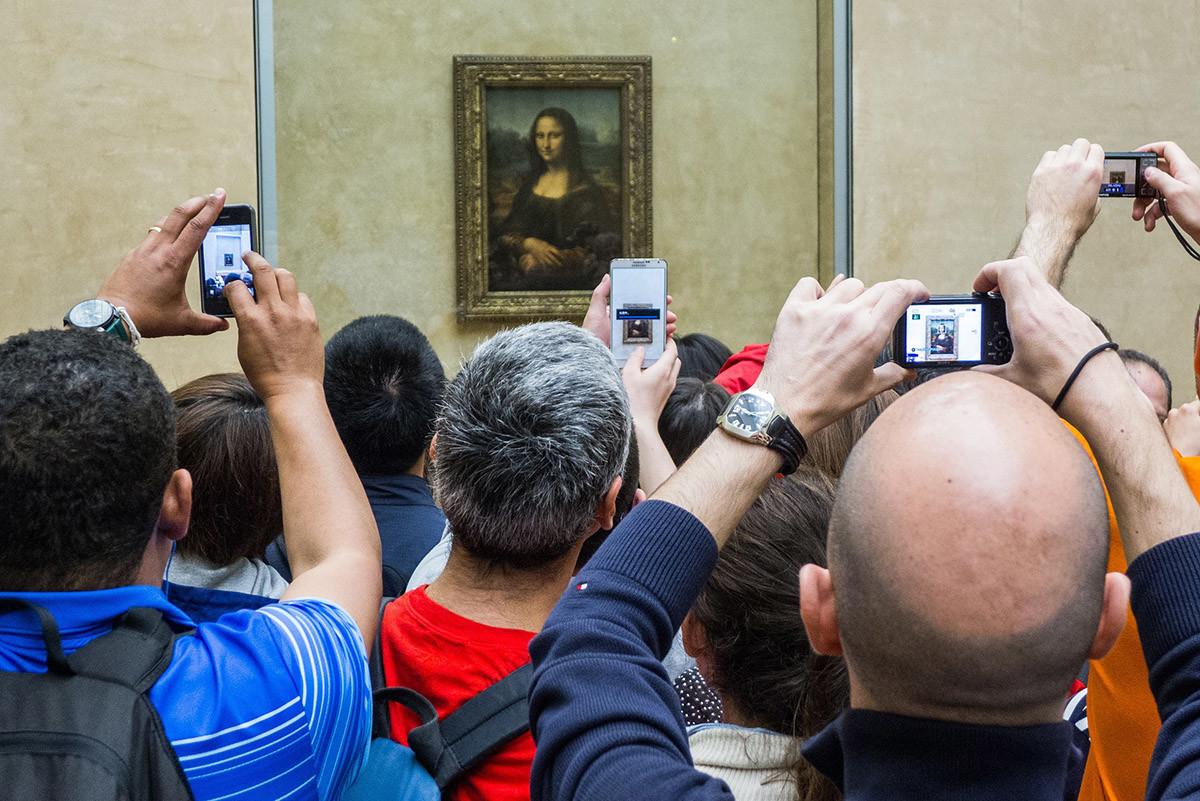 tourists taking a photo of the mona lisa