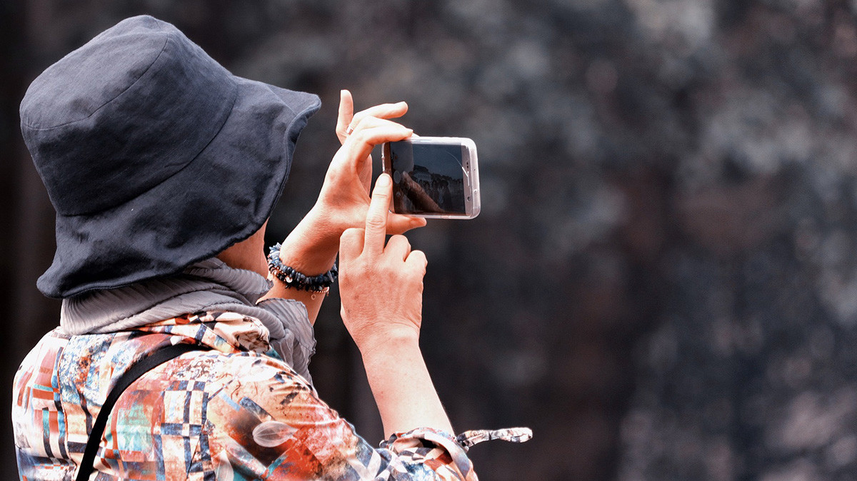 tourist taking a photo with her smartphone