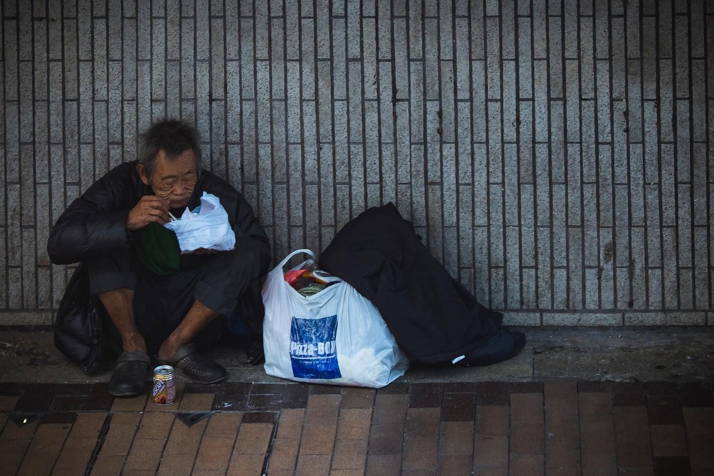 persona pobre comiendo en la calle