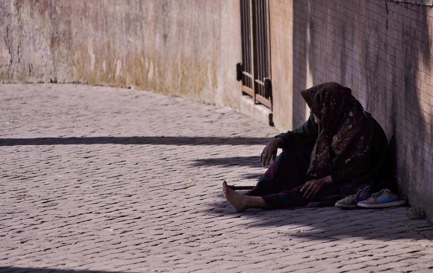 mujer pobre y descalza sentada en la calle