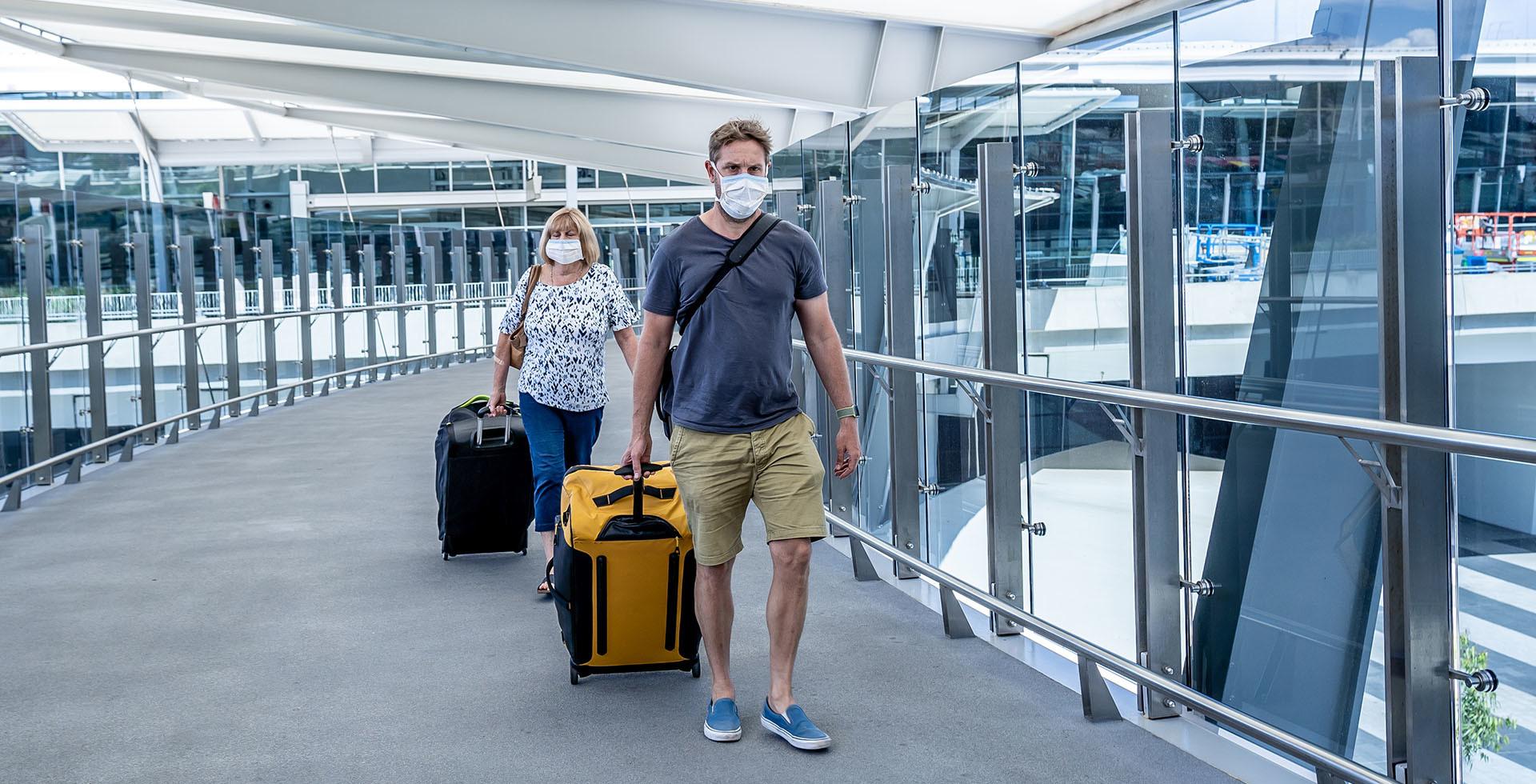 viajeros en un aeropuerto con mascarillas