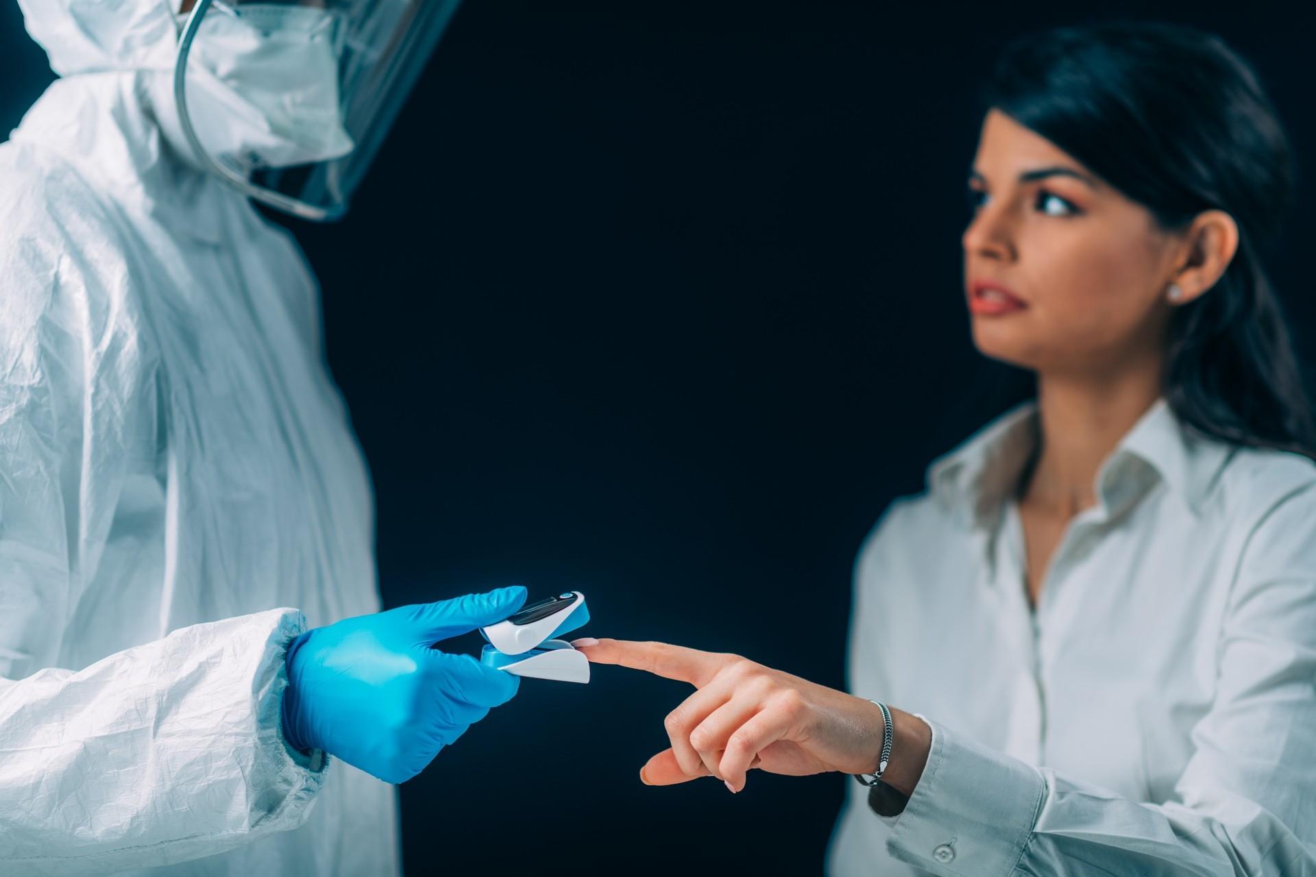 médico midiendo el nivel de oxígeno en sangre de otra persona