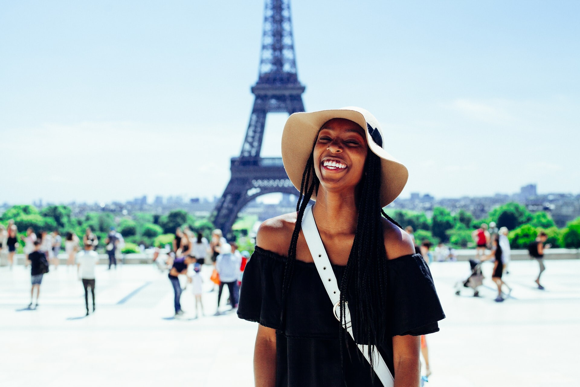 Woman smiling next to the Eiffel Tower