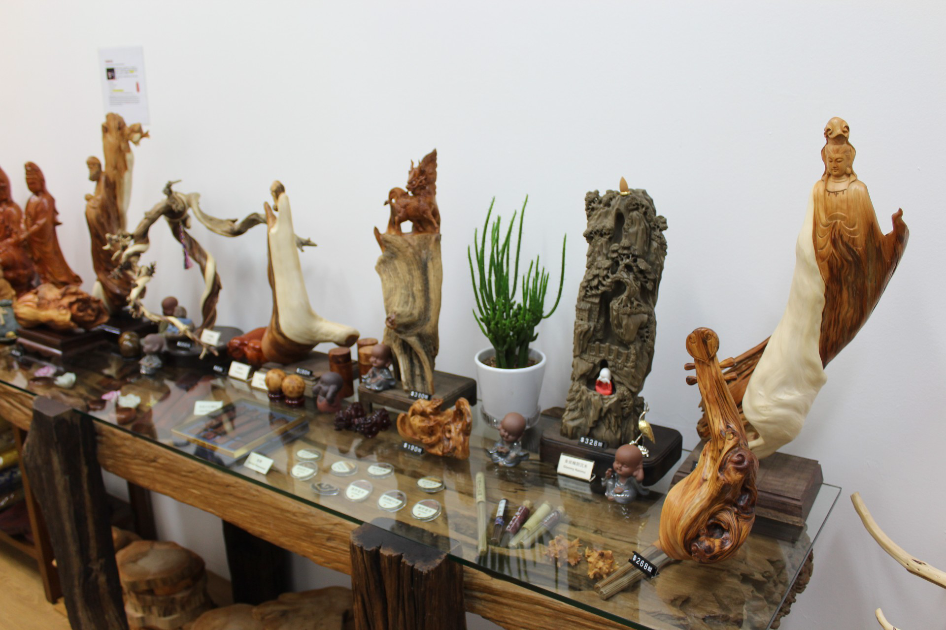 Wooden statuettes on display in Qimu Arts