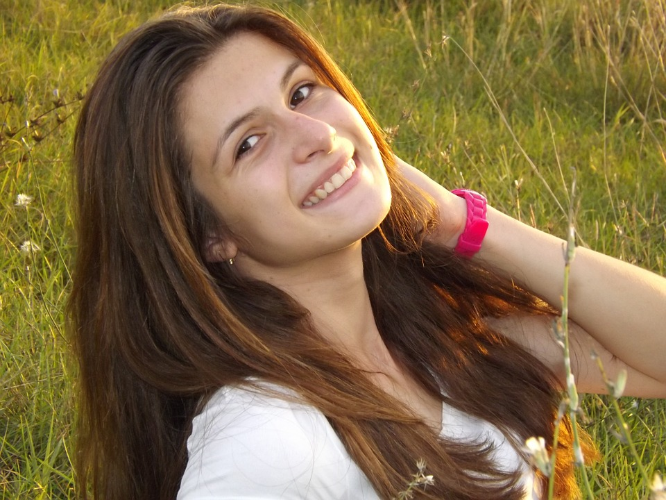 A girl smiling in a field due to good eye health.