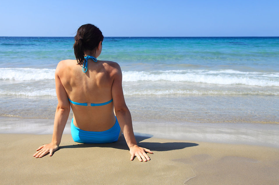 11700-a-beautiful-woman-sitting-on-the-beach-looking-at-the-ocean-pv.jpg