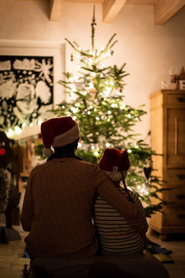 a parent sits by a Christmas tree with their children