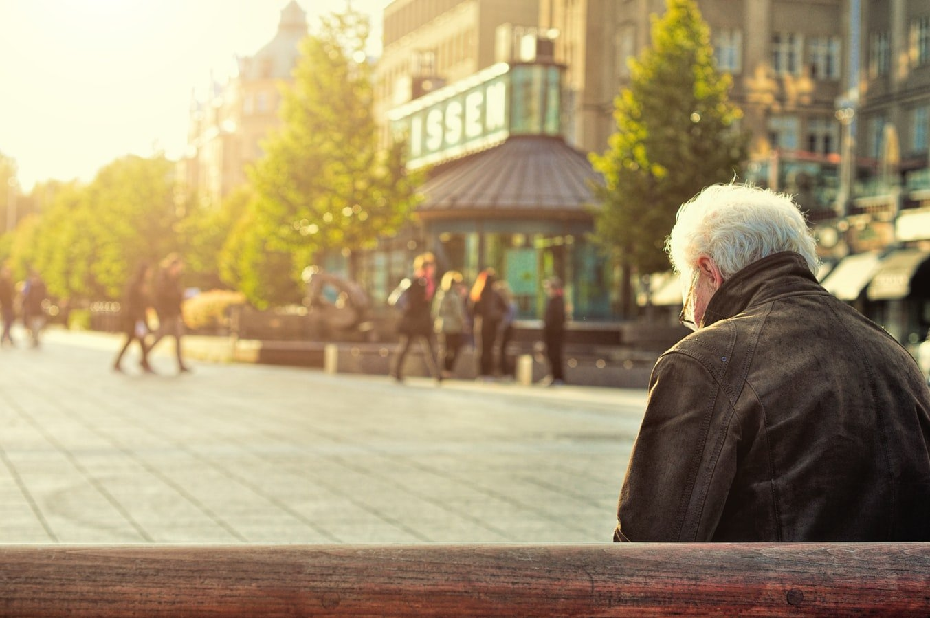 an elderly man sitting alone on a bench