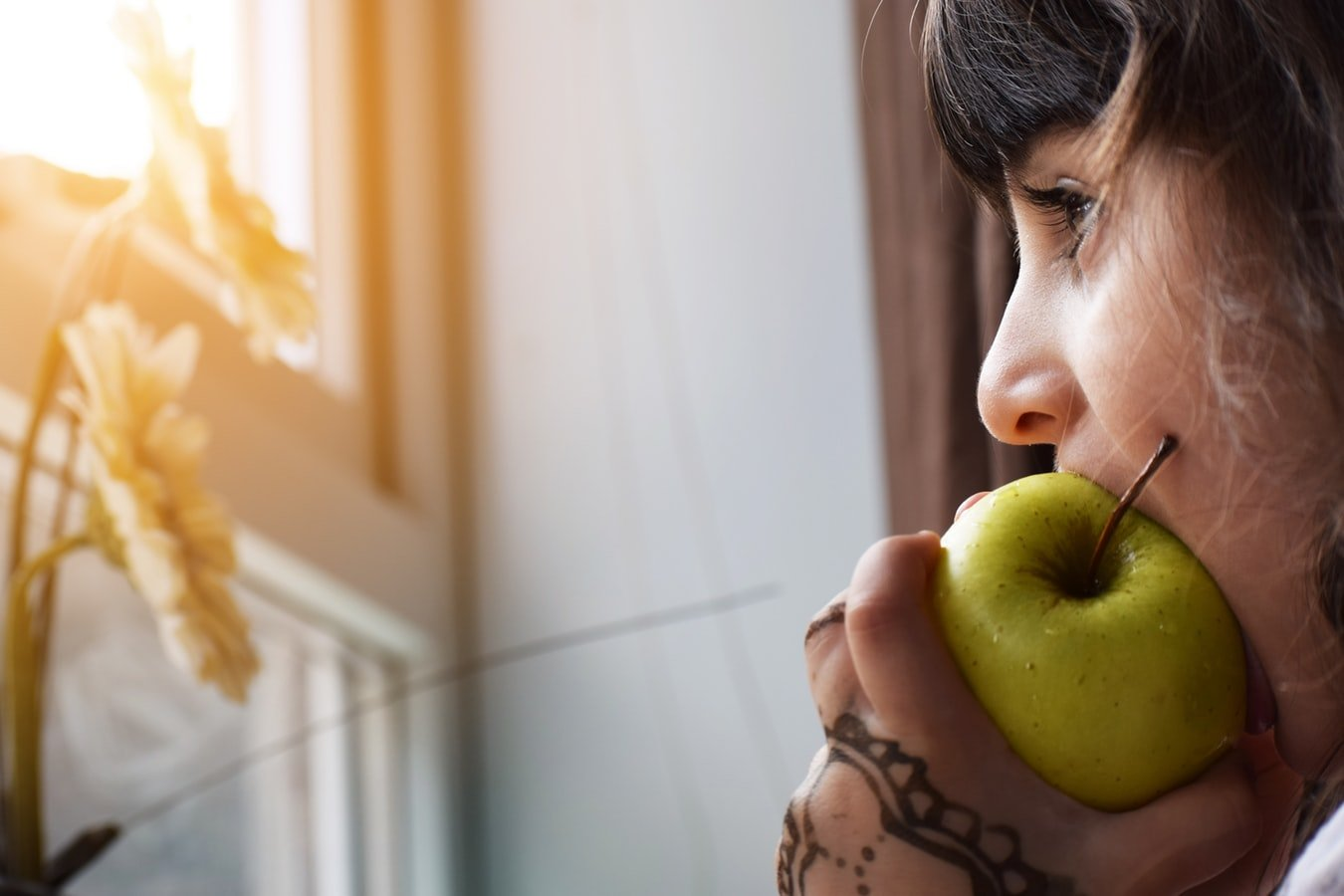 woman eats apple and watches sunset
