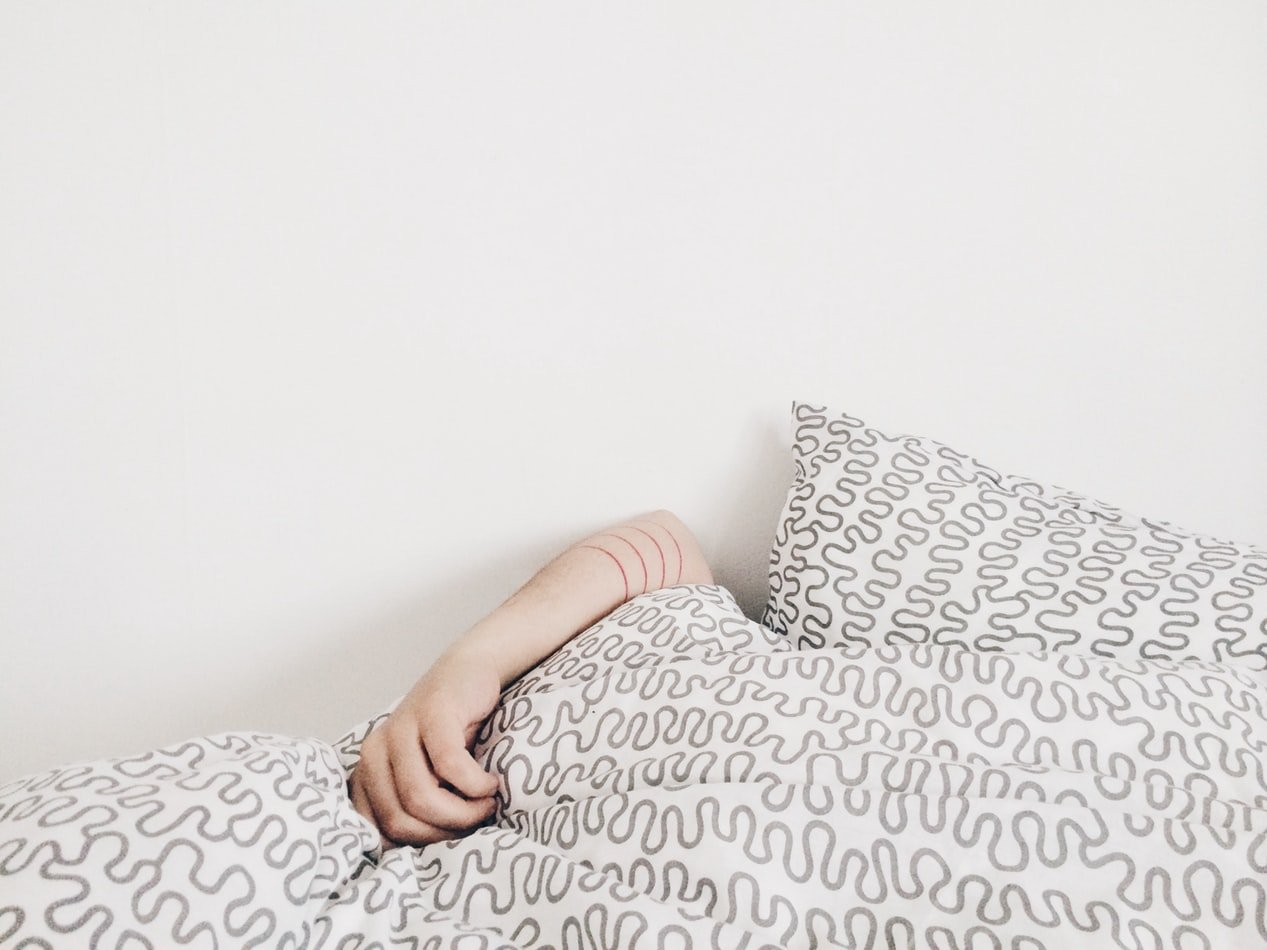 a person sleeps under a patterned blanket
