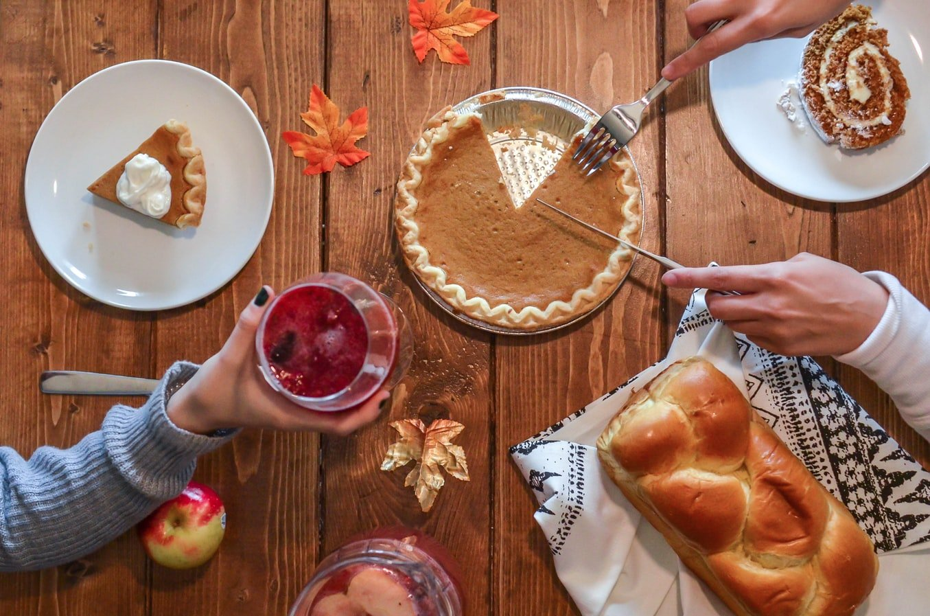 A thanksgiving dinner with fruit, bread, and pumpkin desserts