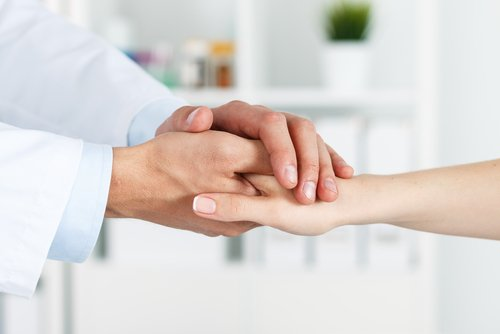 doctor holding patients hands