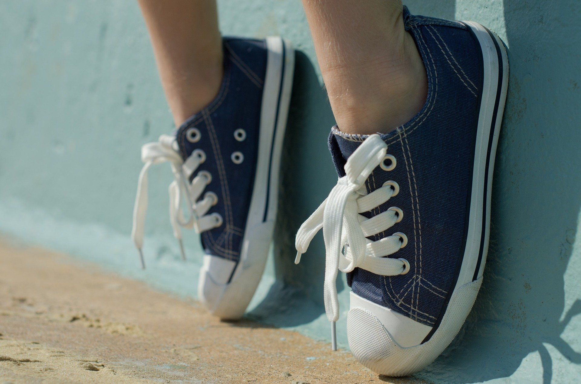 person wearing sneakers rests their feet on blue wall