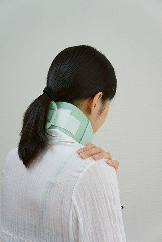 Woman with cervical collar holding her shoulder