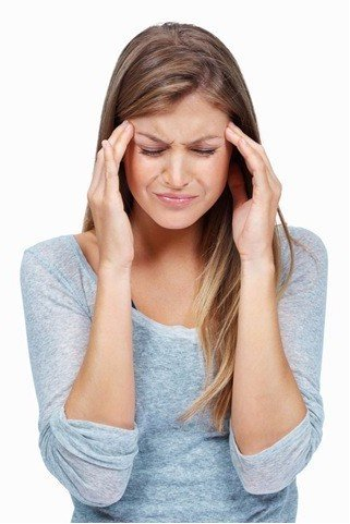 Woman with headache rubbing forehead
