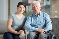 woman with elderly man in wheelchair