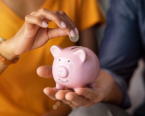 Person Depositing Money into Piggy Bank