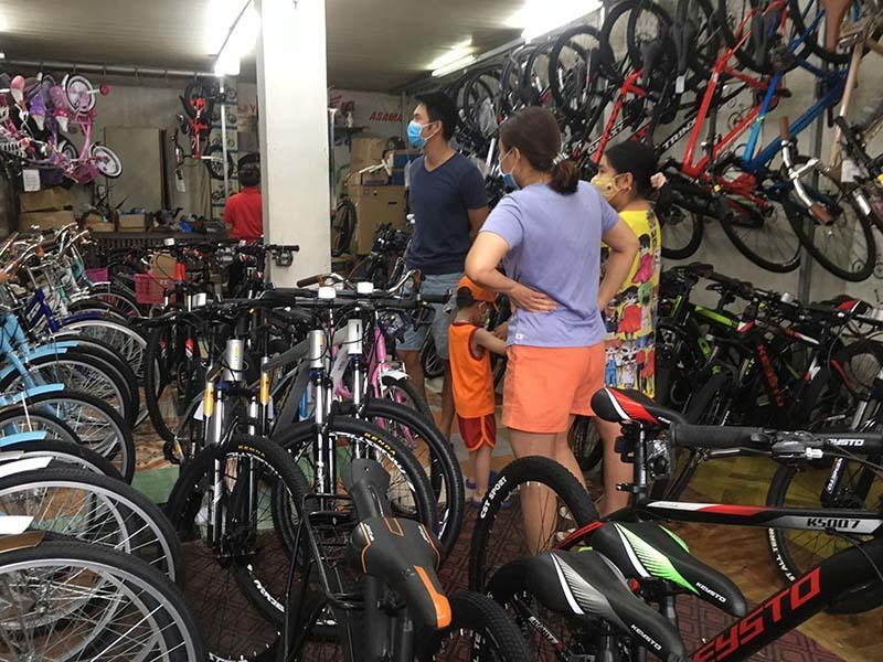 Nhiều phụ huynh dẫn con nhỏ đi chọn mua xe đạp.
