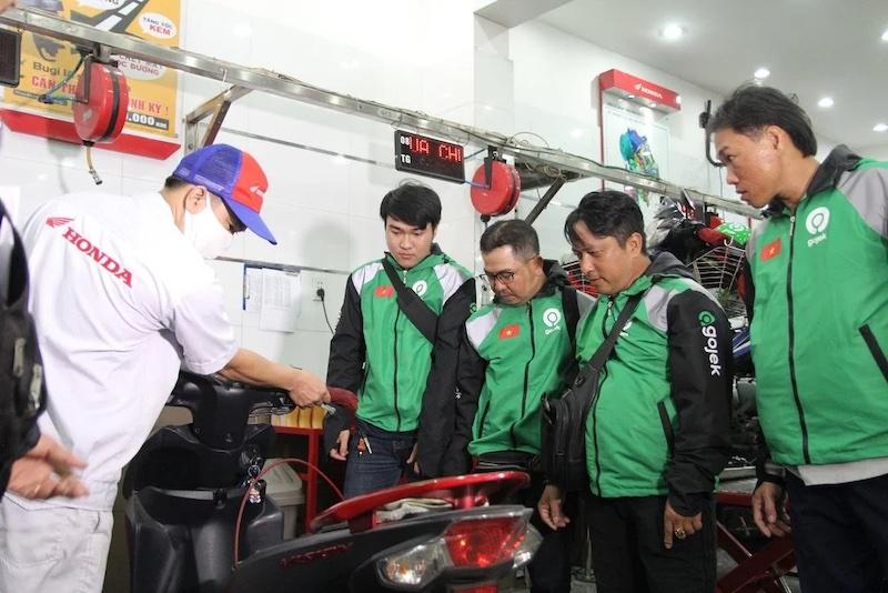 Các đối tác tài xế Gojek đang cùng kiểm tra xe tại cơ sở chuyên nghiệp trong một chương trình hỗ trợ đối tác tài xế của Gojek Việt Nam.