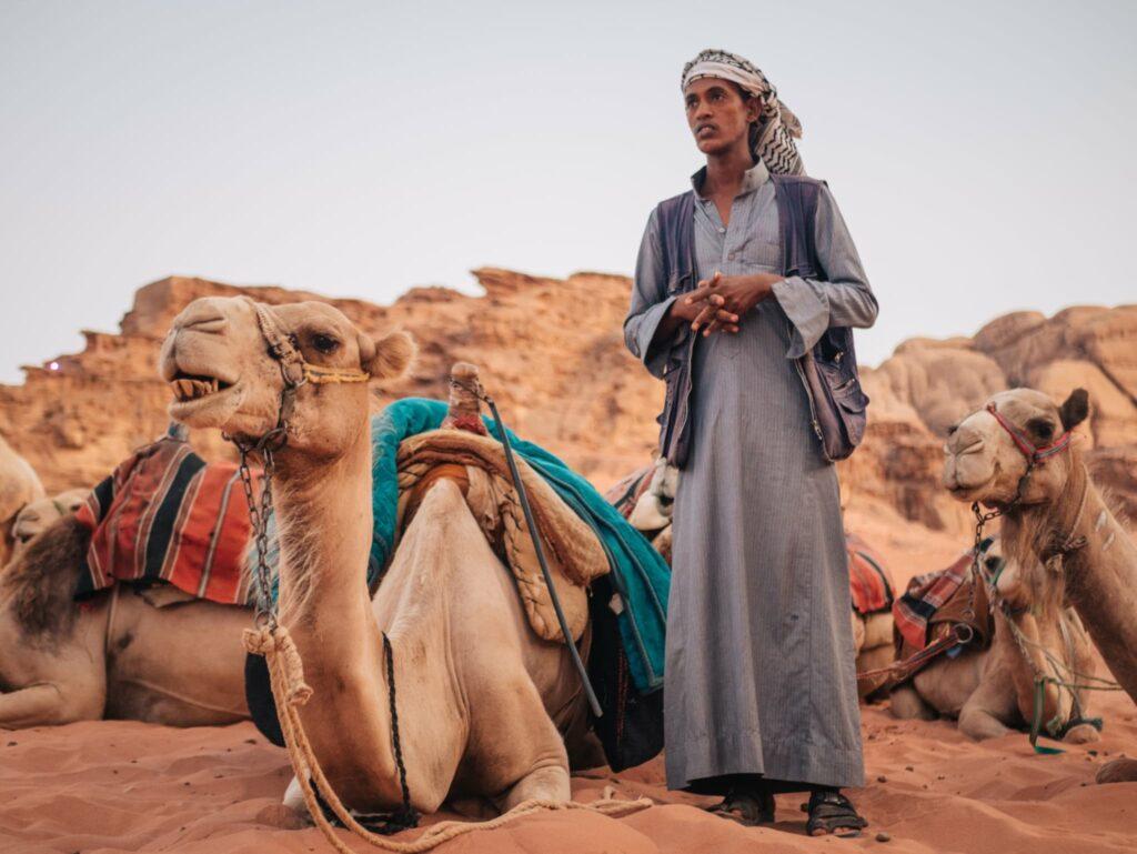A Jordanian standing with his camels in Wadi Rum, Jordan