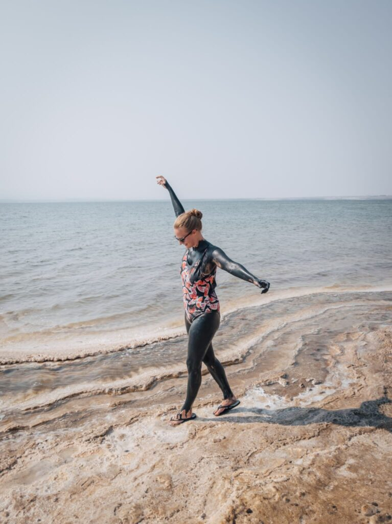 Alexandra Hayward covered in mud and posing with a walk at the Amman dead sea beach