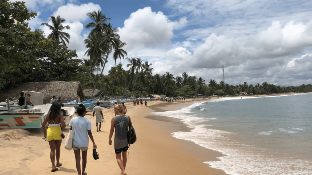 People walking at Arugam Bay beach