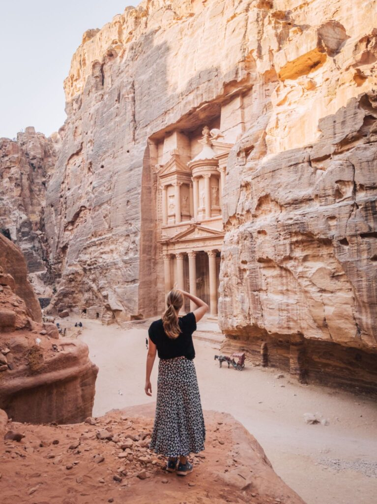 Alexandra Hayward (@findingalexx) standing in front of the Khazneh in the ancient town of Petra in Jordan