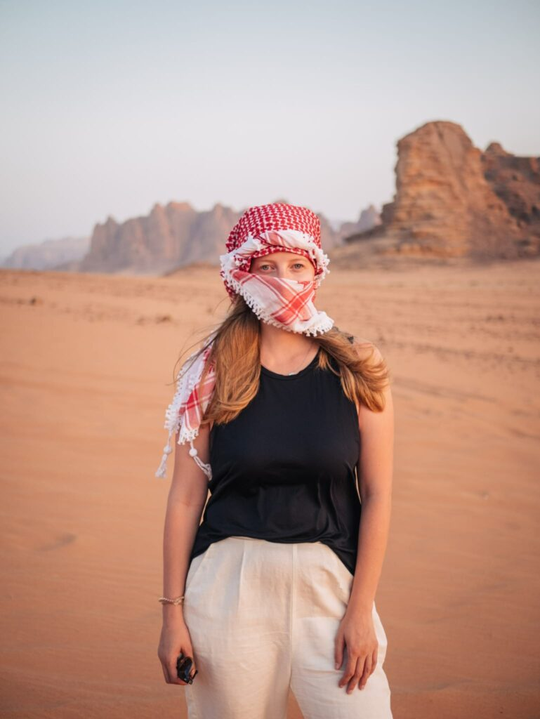 Alexandra Hayward (@findingalexx) standing in the Wadi Rum with an Arab scarf