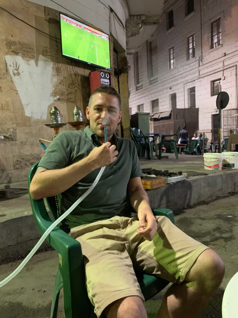 Eivind smoking shisha with a football match playing behind him